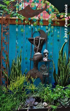 Lucinda is bold with color, painting even her wooden privacy fence to festive effect. Here's her mermaid garden, with blue and green capiz shells creating a watery curtain behind a metal fish and a preening mermaid. Snake plant (Sansevieria) and succulents like 'Sticks on Fire' euphorbia add to the wavy, under-the-sea vignette. • Lucinda Hutson's purple cottage, cantina garden, and Viva Tequila! | Digging