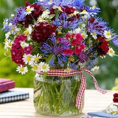 For July 4th centerpieces, try a patriotic palette of flowers gathered into a simple vase or classic mason jar. Tie with a snappy gingham ribbon to finish.