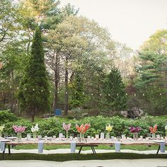 Brides.com: A 1950s-Inspired Styled Wedding Shoot. Whim Events crafted a picnic table from rustic wood slabs and decorated with multicolored snapdragons in vintage hobnail vases. Blue gingham napkins were placed beneath simple white dinner plates.