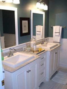 love the stark white cabinets, deep teal walls, white square sinks, and tan counter top...