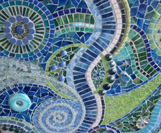Beach Wedding A mosaic that was inspired and created during a beach trip and a wedding. A little feel of the ocean with the blues and then from there it took on its own life, adding a touch of pink and greens. Using a variety of tesserae. Stained glass, handmade pottery pieces, raku shards and a raku donut shaped piece, ceramic tiles, mirror, great little polymer clay tiles from my Etsy friends Betsy (greeegoddess), millefori, glass fishies hidden in there too, little beads & bead f...