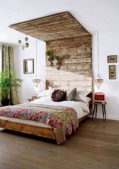 Want your bedroom design to be one-of-a-kind? This rustic wood headboard & canopy definitely achieves that goal! Plenty of plants add to the earthy vibe of this bedroom.