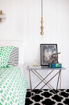 white cottage style bedroom with jade green accents, emerald green, mint green, brass modern pendant light, black and white striped pillowcases, black moroccan patterned rug