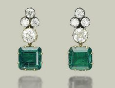 AN IMPORTANT PAIR OF EMERALD AND DIAMOND EARRINGS Set with two octagonal-cut emeralds, weighing approximately 10.01 and 9.36 carats, to the old European-cut diamond surmount and trefoil top, mounted in gold collets with heart-shaped galleries, en suite with lot 215, 3.7 cm