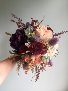 This silk fall wedding bouquet with its rustic detail is perfect for the autumn bride. This handmade bouquet is made with realistic, quality silk flowers and artificial elements. This bridal bouquet is made with burgundy ranunculus, beige and cream hydrangea, dark plum peony, peach and