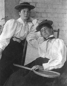 Two women dressed for a game of tennis, 1890-1900. Both wear dark skirts and light coloured blouses with puffed sleeves.The woman on the left has a turned-down collar with a short necktie. The woman on the right's blouse has a high, starched collar. Both women wear straw boater hats perched on top of their hair.