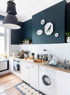 Cuisine en blanc et bleu. J'aime le luminaire de style industriel, le parquet en bois chaleureux, le bleu pétrole des murs (j'adore ce bleu !) et la blancheur immaculée des éléments de cette cuisine.