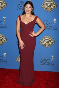 Gina Rodriguez in a dark red, body-skimming red gown