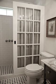 """Says: Instead of an expensive glass shower wall he found an old French pocket door, painted & sealed it multiple times & added tempered shatterproof glass. """"To finish the look and protect the glass from water spots, we placed a poly brocade curtain behind the door,"""" he says. The total costs were just a fraction of the cost of a glass enclosure, and now the shower has a unique architectural element."""