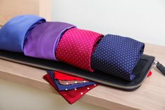 Collection of ties and pocket squares on top of a tie case.