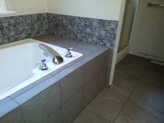 Master bath remodel.  Gray tile with spa mosaic accents.