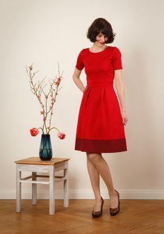 Romantisch schön!  Lotta ist ein zweifarbiges, tailliertes Frühlingskleid mit schmeichelndem Teilungsnähten und schmalen ¾ Ärmeln in rot. Das etwas breitere Taillenbündchen zaubert eine tolle...