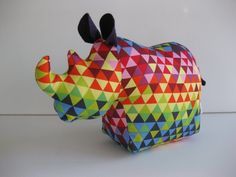 Ronnie Rhino Doorstop  These guys have been a real show stopper and a very popular product.  Ronnie has several uses but is always keen to guard your door or hold up your books. Made from hard wearing duck cloth fabric he has a well weighted sand bag (approx. 2kg) in the base so no more stubbing your toe on a hard iron or wooden door stopper.  Ronnie features a rainbow triangle pattern body with dark purple felt ears and tail.  Measuring approx. 25cm H x 37cm L x 14cm Fat tummy he is of…