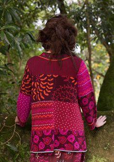 Dit prachtige jacquardgebreide vest van iets steviger biokatoen is als een droom van dessins. Mooi samengesteld met een overslagsluiting, twee handige zakken en borduursel rond de halsopening.