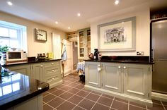 """KITCHEN  4.06m x 3.28m, 13'4"""" x 10'9"""", 4.06m x 3.28m (13'4"""" x 10'9"""") The heart of the modern home, this immaculate and pleasant kitchen features solid-wood, hand-painted, bespoke units including French-style display cupboards, low and high-level units with granite work-tops and a Belfast Sink. Space and plumbing is provided for a dishwasher and the kitchen has an integral Baumatic electric 4-ring hob and a Siemens fan assisted electric oven below."""