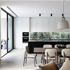 Uma #cozinha perfeitamente integrada tanto com o #living - em tons de cinza e bege - quanto com o exterior, graças às aberturas de vidro no fundo na bancada. No projeto dos arquitetos do Canny (@cannygroup), destaca-se ainda a bela ilha central em granito negro, assim como a expressiva luminária pendente Bell Lamp, da Normann Copenhagen (@normanncph). #decoração #architecture #design #reforma #retrofit #arkpad #decor