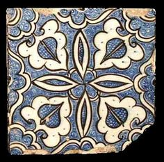 Egypt or Syria.   A square stone paste tile freely painted in underglaze blue and black. Four ogivals in white, each with a central onion motif, outlined in black, face inwards from each corner between each leaf of a central simple four-leafed design also in white and outlined in black. The remaining area completely filled with blue cross hatching and tight cloud/wave patterns. First half of the 15th century.