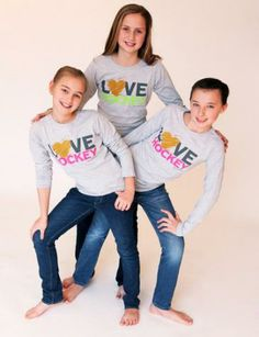 "Love Hockey - Long Sleeve T | Bee Fearless Great for layering for practice or simply worn with jeans, our oh so soft heather grey long sleeve hockey t shirt is the perfect way to express your love of the sport!     Choose from pink or lime lettering with some extra gold heart-felt bling!  Junior sizes offer a slimmer, longer fit to accommodate lot o' sizes. A ""must have"" for fearless hockey girls!   Sizes - Junior Small, Medium, Large, Xtra Large"