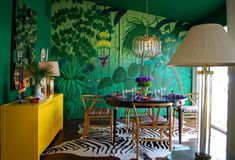 GOING WILD! In diesem Esszimmer wurde das Dschungelthema ernst genommen und damit ein aussergewöhnlicher und eleganter Raum geschaffen. Eine Wand mit einer Motivtapete, die anderen in einem passenden Grünton, dazu das sonnengelbe Sideboard als perfekter Kontrast – so schafft man ein filmreifes Wohnambiente.
