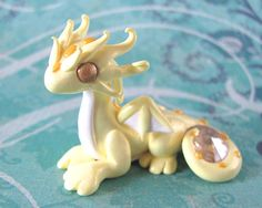 This little dragon is the ninth in my Gem Dragons series. He is made of high quality colored polymer clay, and finished with a gloss sealant. He is a shimmery yellow with pale yellow accents. His tail is curled protectively around a citrine swarovski crystal. He is a little under 2 inches tall.