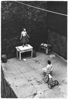 girl standing on desk in courtyard, performing for a seated girl, c.1955 • wiliam gedney