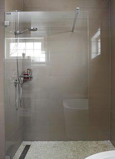 Dusjen er enkel, og nesten usynlig med den rene glassdøren. Den matte gråfargen på flisene skaper en rolig atmosfære. Flisene på gulvet er mer detaljrik, og blir derfor en spennende effekt.