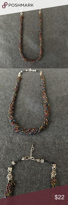 """Multi-Strand Glass Seed Bead Necklace This beautiful necklace is comprised of Multiple strands of hand-strung glass beads in a variety of colors.  As the pictures depict it includes deep red, cobalt blue, clear & metallic green, black, gold & purple.  The length is adjustable by 1"""" and can be worn anywhere from 24"""" up to 25"""" in Total length.  Purchased at an Art Show- It is a Handmade necklace and done by SF Bay Area Artisan.  Was purchased as a gift for $50, but never given.   No tags, no…"""