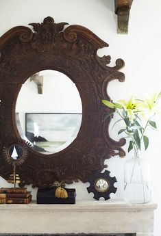 Inside a Bungalow That Maximizes Its Small Space// mantle piece styling, carved wood mirror