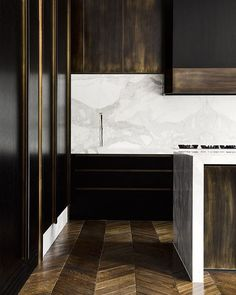 Handsome kitchen in deep, warm woods and marble.
