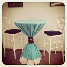 A very unique cocktail table setup! A white linen layered with a turquoise linen, a brown sash, and a sparkling brooch.