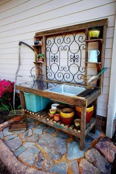 Lisa Fay is another lucky gardener, whose husband was able to build a 'creating space' for her. An fancy iron railing pice is the star feature and the flagstone patio echoes the shapes. A slated shelf drains easily and shelves on either side hold necessaries.