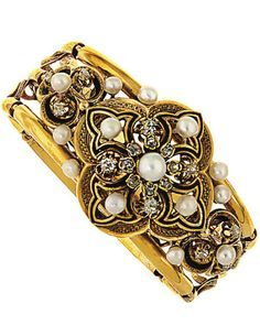 A 19th century gold, pearl and enamel bangle The hinged openwork bangle with central quatrefoil motif set with brilliant-cut diamonds and natural pearl accents, with black enamel line detail to similarly decorated shoulders, circa 1880, inner diameter approximately 6.0cm