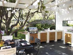 Une cuisine d'été tout confort sous une tonnelle construite en dur avec murs en parpaings blanchis et toit en bois
