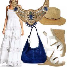 Abito lungo ricamato, scarpe con zeppa in sughero, borsa blu scamosciata, cappellino in paglia. L'outfit è impreziosito da una collana con richiami in blu.