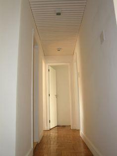 Com 90cm de largura, liga a sala à área íntima. No teto, trabalho em madeira pintada de branco que esconde um prático maleiro.