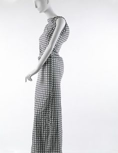 This is from the Lumps and Bumps collection by Comme des Garçons. The designer, Rei Kawakubo, designed this in SS 1997 in Japan. It is made of nylon and polyurethane. Under the check-print over dress, there is an under dress that has built in padding on random areas of the body. There is some wrapping around from one hip to the butt and more on the back, like a hunchback look.