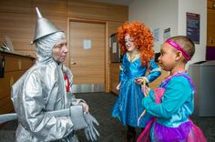 A Jimmy Fund Clinic staff member dressed as the Tin Man stops to chat with two young patients during the clinic's annual trick-or-treat event.