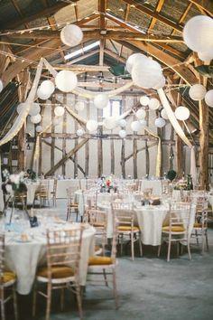 Géniale cette idée déco pour décorer une salle de réception dans un style cosy et tendance. Que cela soit un grand espace industriel ou bien une grange pour un mariage campagne chic, les guirlandes lumineuses et les lanternes japonaises marchent à tous les coups ! Ici en blanc, mais elles peuvent évidemment se décliner dans les couleurs de votre choix. Alors, vous aimez ?