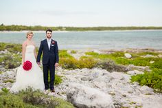 Bride and Groom. Rocks, ocean, Navy suit, Vera Wang. Photographer - Dean Sanderson