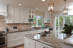 white painted shaker kitchen cabinets, granite island, grey quartz countertop, pendent lighting, travertine backsplash