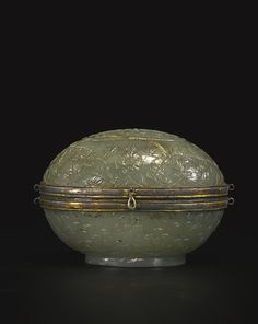 A MUGHAL CELADON JADE BOX AND COVER INDIA, 18TH / 19TH CENTURY of oval form, the box carved in low relief with floral scrolls, the design repeated on the domed cover to encircle a panel of stylized floral sprays, the mouthrims mounted with Indian or Turkish hinged metal mounts, the stone of a celadon color with fissuring and milky-white inclusions