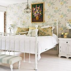 Traditional Cottage sure is looking gorgeous here...a mix of vintage wallpaper...antique bed...shabbied furniture...pillow accents (again mix and match with a common color thread)...and interesting chandelier..white washed flooring all adding up to this seriously divine look.