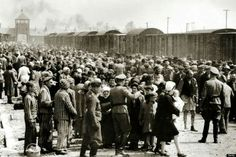 Original photo of Hungarian Jews being unloaded on the platform at Auschwitz with smoke from the ovens in the background, 27 May 1944.  Shame on Germany, shame on the world!