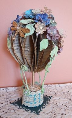 Altered Book.  This is an altered art book Hot Air Balloon!  I have honeycombed the pages.  All flowers are hand made water distressed.  It is embellished with a dragon fly.  Butterflies are enjoying the blooms.