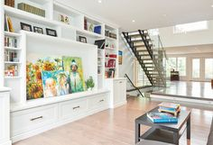 """White built-ins in family living area show collectables and bright family artwork.   See more of this home in """"Bright Home on Secret Ottawa Lake Goes Modern"""" from OUR HOMES Ottawa Summer 2016 http://www.ourhomes.ca/articles/build/article/bright-home-on-secret-ottawa-lake-goes-modern"""