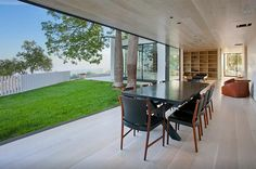A formal dining room or an open air setup sits beside the lawn in the wood lined space.