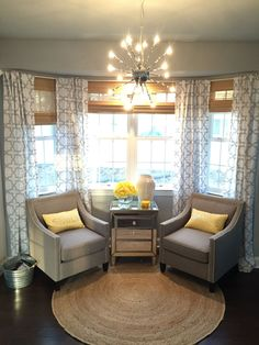 This is one of my favorite spots in my home my bay window with two beautiful neutral taupe linen chairs with chrome nail head detailing. The curtains are white linen with gray quatrefoil print. The roman shades are all natural bamboo from Home Depot home decorators collection. The white bay window rods are from bed bath and beyond I choose white to got with the trim on the first floor and too keep it bright The mirrored 3 drawer chest vases and candle all from homegoods  finished with a jute…