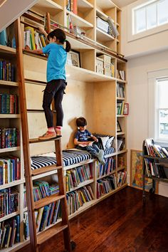 Room with wood bookshelves, wood ladder, wood floors, black and white striped bench, white walls, and an assortment of children's books