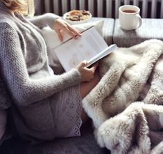 comfy cozy woman snuggled up with a knit sweater reading and drinking a coffee