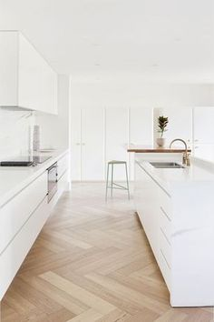 This lovely chevron wood floor adds warmth to this all white kitchen.